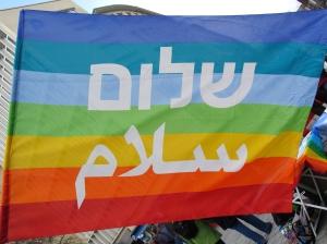 2013-03-30_Ostermarsch_Hannover_vom_Kröpcke_aus,_Regenbogenfahne_Frieden_Peace_hebräisch_Schalom_arabisch_Salam